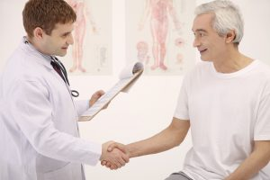 doctor and elderly patient shaking hands and smiling