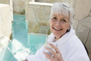 senior woman drinking by pool