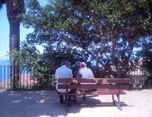 two elderly men sitting on a bench talking