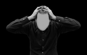 man grabbing head without clear identity