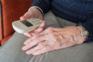 elderly man looking at cordless phone