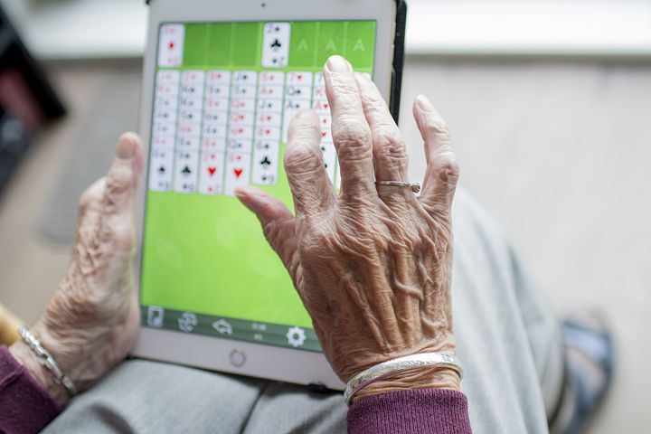 Elderly person playing digital card game
